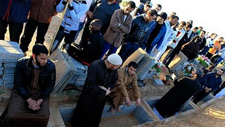 Libyans mourn during the funeral of people who were killed after air strikes, in Tripoli on Sunday, March 20, 2011.