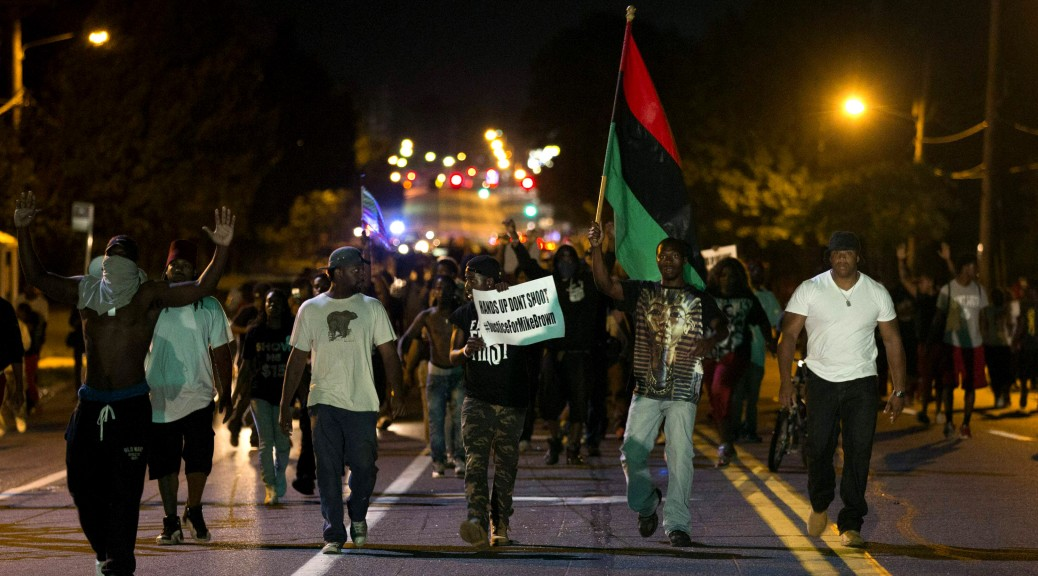Demonstrators march in the street while protesting the shooting death of black teenager Michael Brown in Ferguson